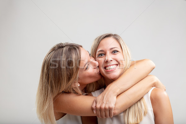 Two happy young girlfriends or sisters kissing Stock photo © Giulio_Fornasar