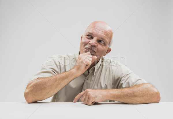 Pleased man sitting thinking with a smile Stock photo © Giulio_Fornasar