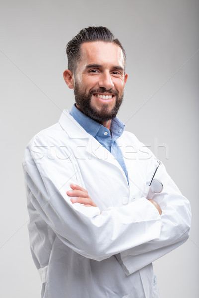 Smiling confident male doctor in a white lab coat Stock photo © Giulio_Fornasar