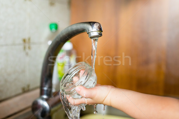 Stock photo: hand of a child with container under water