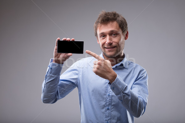 Foto stock: Sonriendo · amistoso · hombre · senalando · móviles · teléfono · móvil