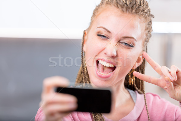 Young woman cheering as she takes a selfie Stock photo © Giulio_Fornasar