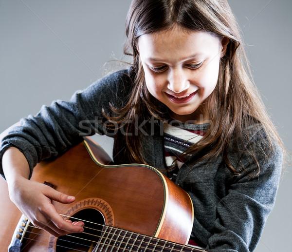Sorridente menina jogar clássico violão acústico Foto stock © Giulio_Fornasar