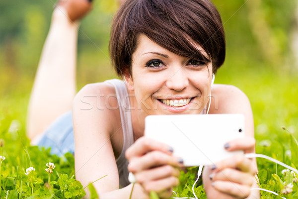 Foto stock: Sorridente · feliz · mulher · ouvir · música · ao · ar · livre · estômago