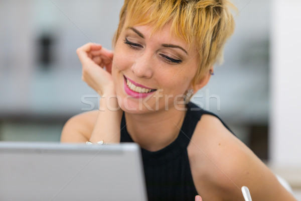 Smiling young woman looking at laptop Stock photo © Giulio_Fornasar