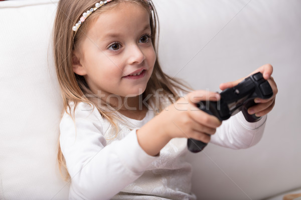 Cute little girl having fun playing video games Stock photo © Giulio_Fornasar