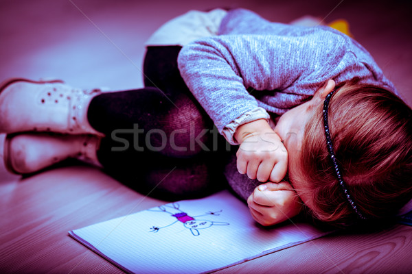 Upset little girl curled up next to her drawing Stock photo © Giulio_Fornasar