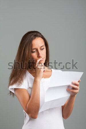 Thoughtful young woman reading a document Stock photo © Giulio_Fornasar