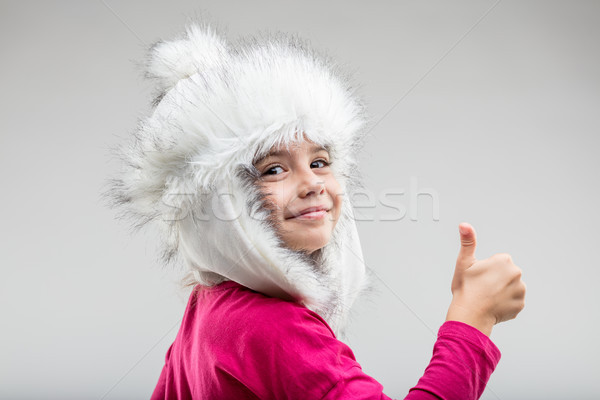 Preteen girl wearing fluffy cap giving thumb up Stock photo © Giulio_Fornasar