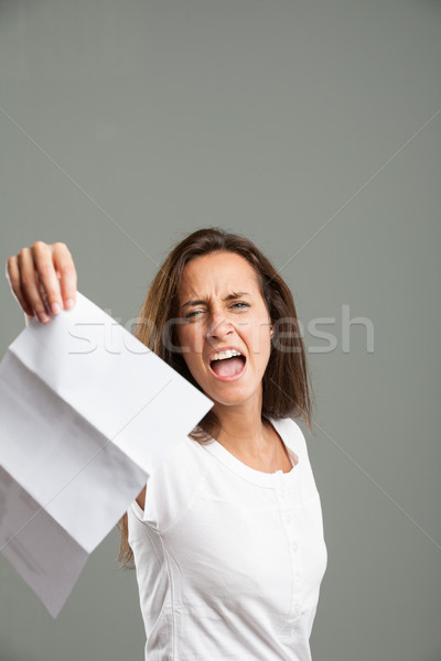 Distressed young woman holding up a document Stock photo © Giulio_Fornasar