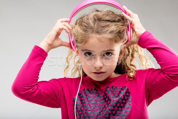 L girl listening to music on pink headphones Stock photo © Giulio_Fornasar