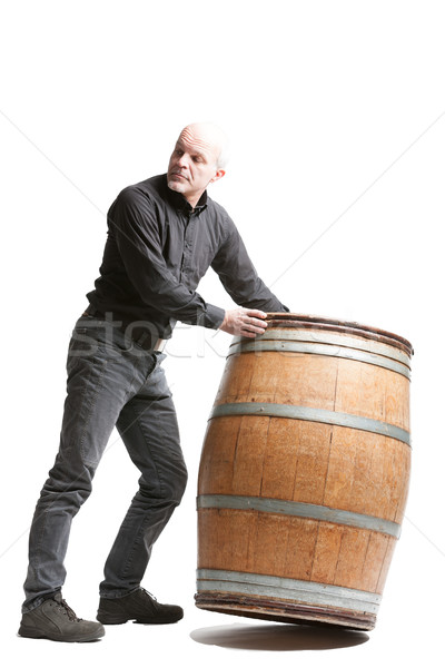 Middle-aged man tilting a wooden cask or barrel Stock photo © Giulio_Fornasar