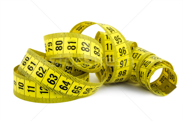 Curled yellow measuring tape on white background Stock photo © Givaga