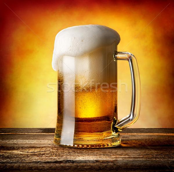 Kubek piwo jasne pełne drewniany stół świetle szkła tle Zdjęcia stock © Givaga