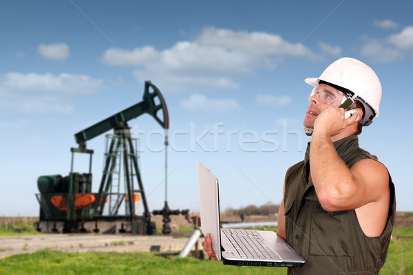 Stock photo: oil worker with laptop and phone