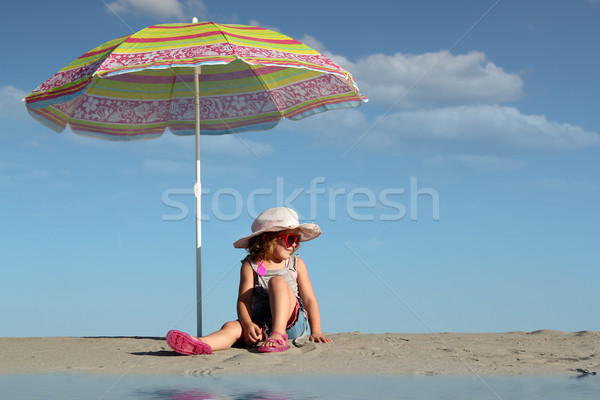 little girl with sunglasses sitting under sunshade Stock photo © goce