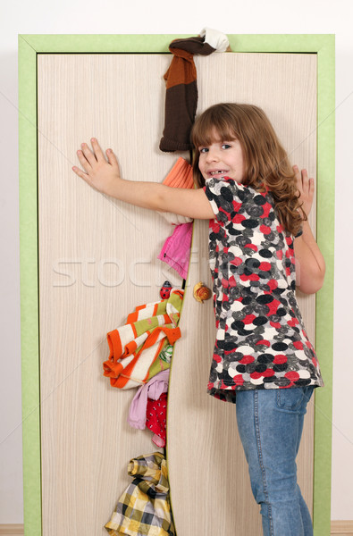 upset little girl trying to close the closet  Stock photo © goce