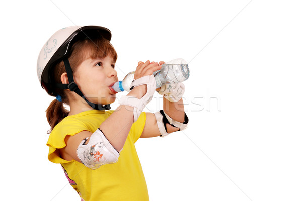Stock photo: little girl with protective gear drink water
