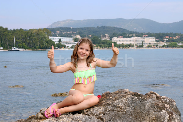 Stock photo: happy little girl with thumbs up on summer vacation