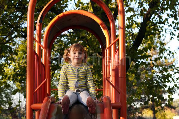 Belle petite fille séance aire de jeux slide sourire Photo stock © goce