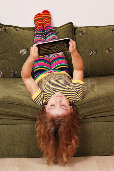 little girl lying upside down on bed and play with tablet Stock photo © goce