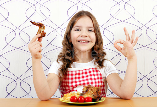 happy little girl with roasted chicken wings and ok hand sign Stock photo © goce