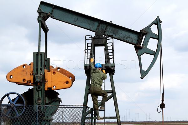 oil worker climbs to the pumpjack Stock photo © goce