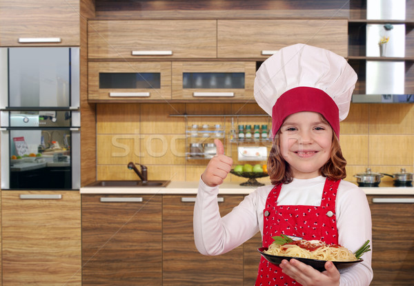 happy little girl cook with spaghetti and thumb up in kitchen Stock photo © goce