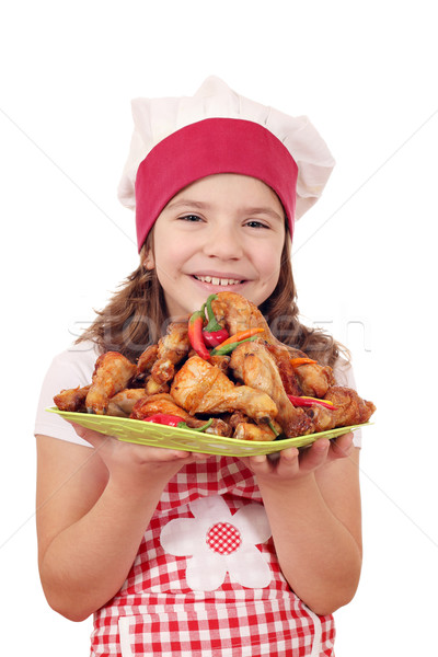 happy little girl cook with roasted chicken drumstick on plate Stock photo © goce