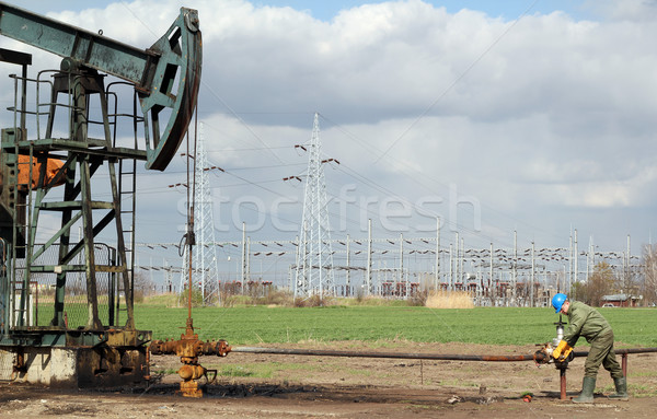Stock photo: oil field with pump jack and worker