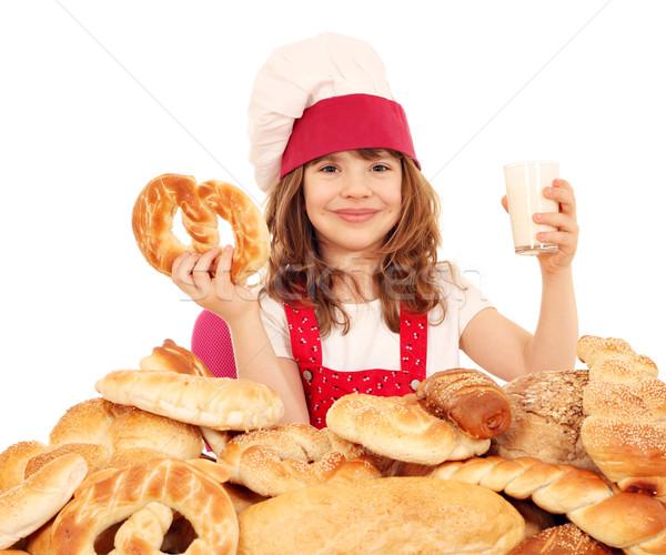 Feliz little girl cozinhar pretzel vidro leite Foto stock © goce