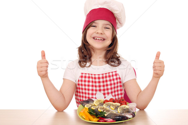 happy little girl cook with fish and thumbs up Stock photo © goce