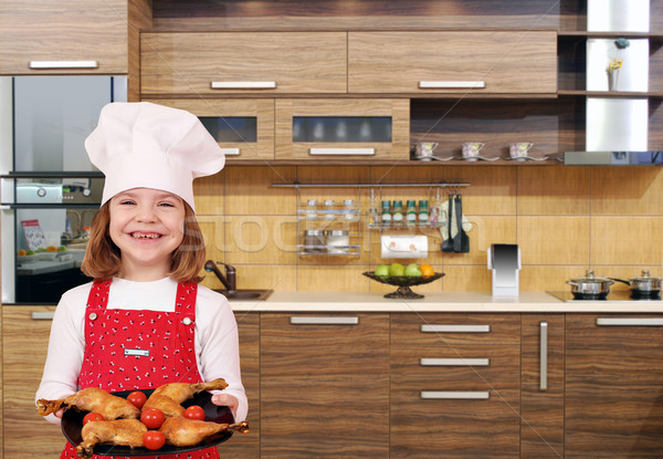little girl cook with chicken drumstick in kitchen Stock photo © goce