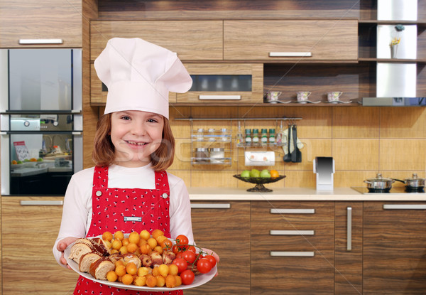 happy little girl cook hold plate with gourmet food in kitchen Stock photo © goce