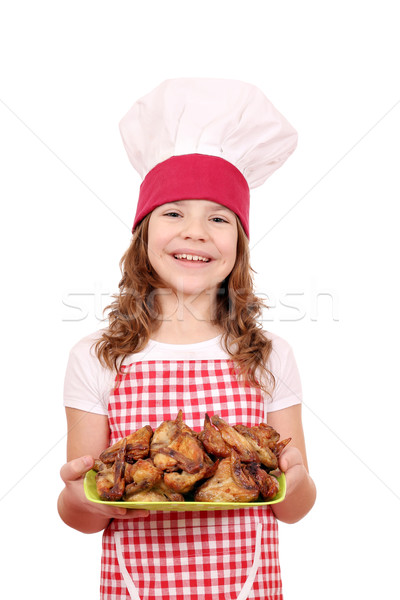 happy little girl cook with chicken wings on plate Stock photo © goce