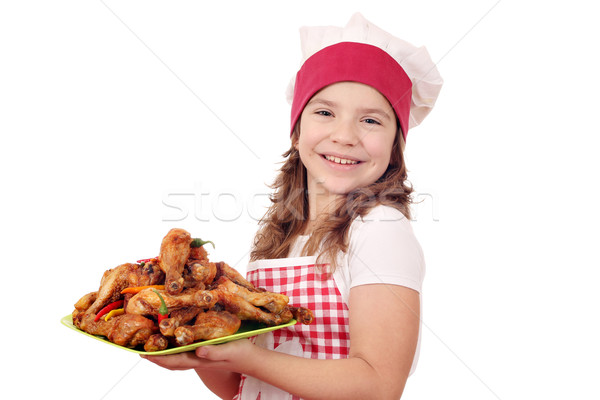 happy little girl cook with chicken drumstick on plate Stock photo © goce