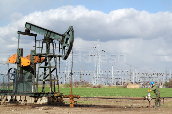 oil field with pumpjack and oil worker Stock photo © goce