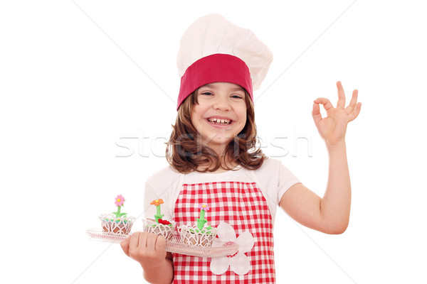 happy little girl cook with spring flowers muffins and ok hand s Stock photo © goce