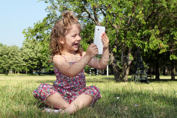 happy little girl with tablet in park Stock photo © goce