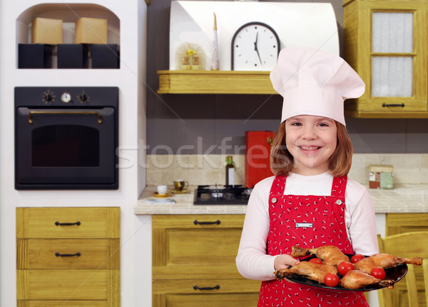 happy little girl cook with delicious chicken drumstick in kitch Stock photo © goce