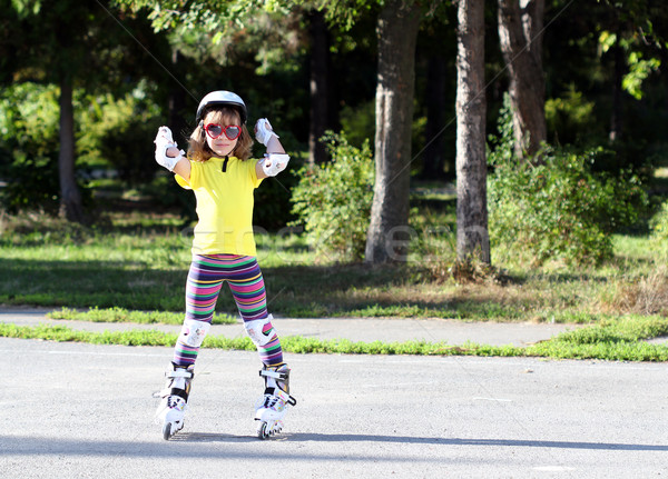 Roller skating happy little girl with protective gear Stock photo © goce