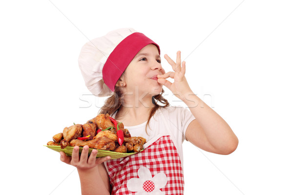 happy little girl cook with chicken drumstick and ok hand sign Stock photo © goce