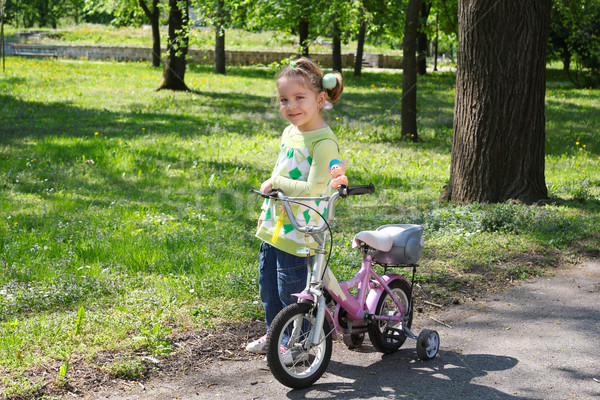 little girl with bicycle posing in park Stock photo © goce