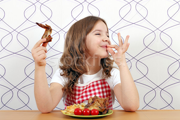 happy little girl with chicken wings and ok hand sign Stock photo © goce