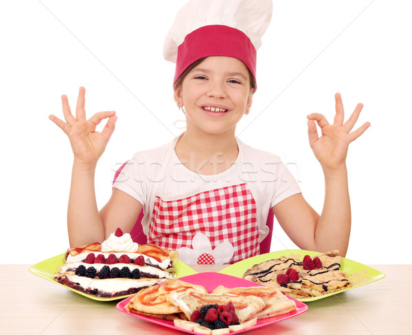happy little girl cook with delicious crepes on table and ok han Stock photo © goce