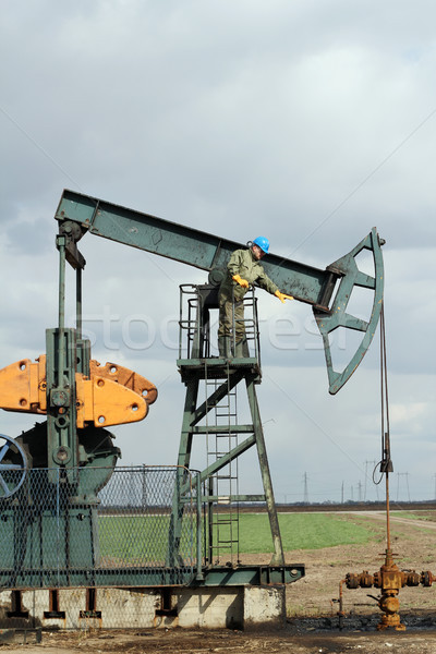 oilfield with worker and pump jack Stock photo © goce