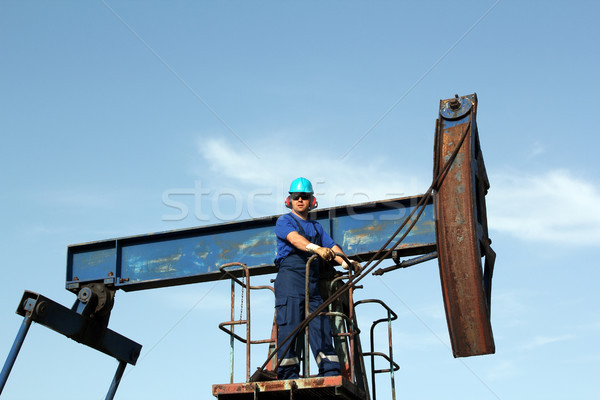 oil worker with sunglasses standing at pump jack Stock photo © goce