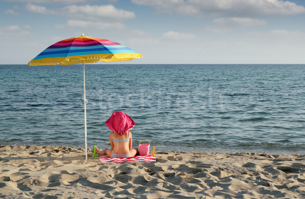 little girl with hat sitting under sunshade on beach Stock photo © goce