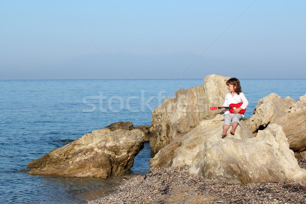 little girl sitting on a rock by the sea and playing guitar Stock photo © goce