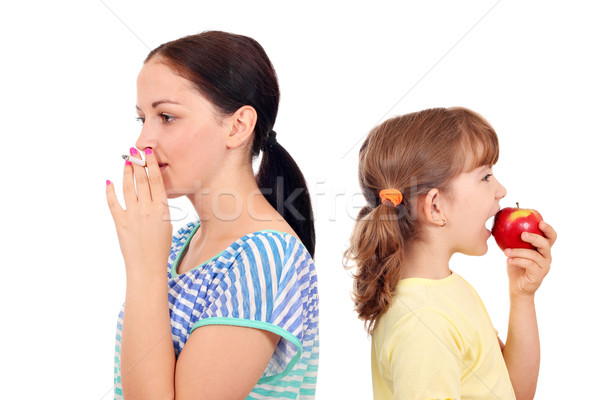 Stock photo: girl smoking a cigarette and little girl eating an apple